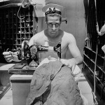 Cecil Beaton - A sailor on board HMS Alcantara uses a portable sewing machine to repair a signal flag during a voyage to Sierra Leone - © Cecil Beaton/ Imperial War Museum