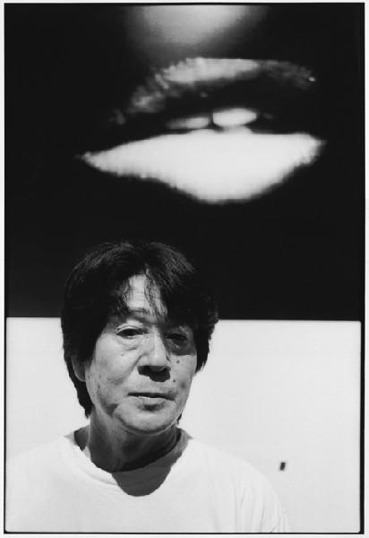 Daido Moriyama - Moriyama beneath his photo of lips, Tokyo, 2003.