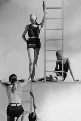 Two men wearing bathing suits (jersey tank tops and belted trunks) climbing up ladder toward two models (the one standing on the left is Georgia Graves) wearing belted one-piece jersey bathing suits (Ondine) with stripes on the bottom; designed by Lucien Lelong; bathing caps